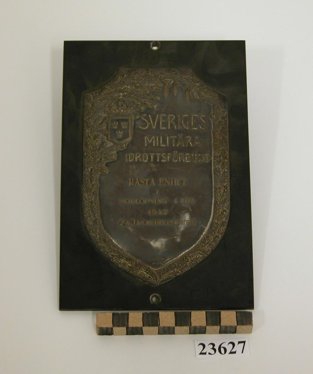 Plakett av silver i form av vapensköld fäst på platta av bakelit. Längs sköldens kant dekor föreställande granris samt tre hängande grankottar. I sköldens övre vänstra hörn en liten vapensköld med tre kronor, krönt av kunglig krona. Text på plaketten: SVERIGES MILITÄRA IDROTTSFÖRBUND TILL BÄSTA ENHET I SKIDLÖPNING 1942 2:A JAGARDIVISIONEN. Se SSS och X pärm.