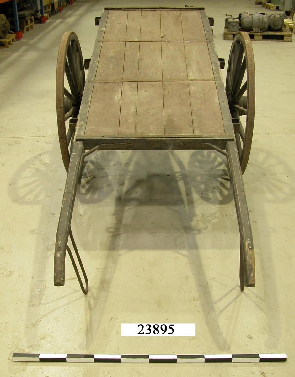 Kärra av trä med två hjul och fjädring. Beslag av järn. Flak av trä, röd-brunt målat. Hjul av trä. Fjädring och slitskena på hjulen av järn. Stödben av järn. Hjul och kanter är svartmålade. På flakets långsidor sitter tillsammans sex beslag för montering av kragar/sidstöd.