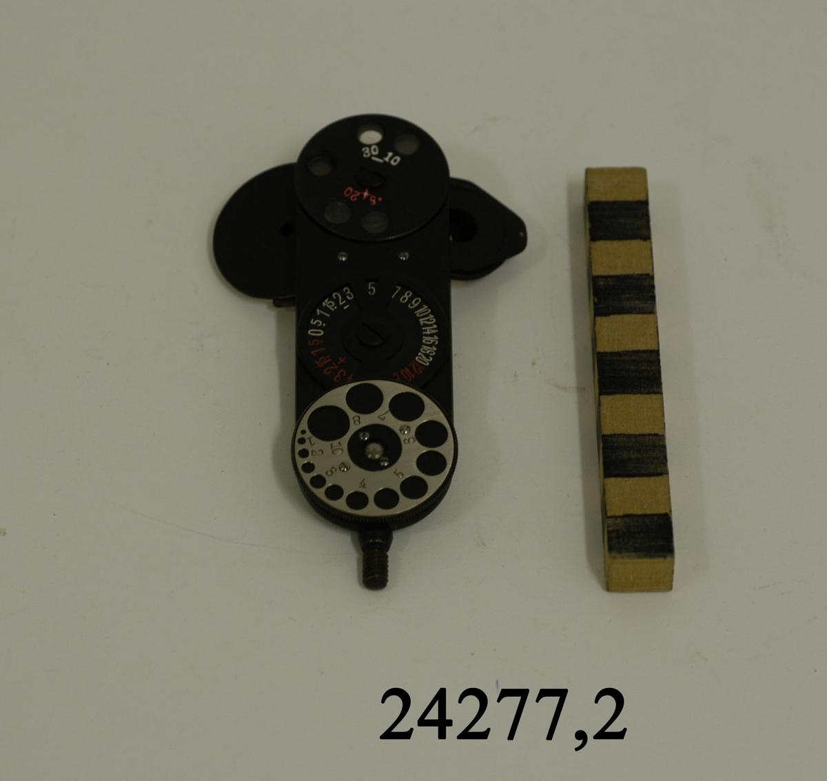 Ögonspegel. Platt, svart, rektangulärt metallplatta med rundade kanter. I ena änden en gängad stav för fästande av handtag. På plattans ena sida två stycken runda, rörliga speglar. Den ena större än den andra. På plattans andra sida tre stycken rörliga, graderade skivor. Den övre består av linser i olika styrka.