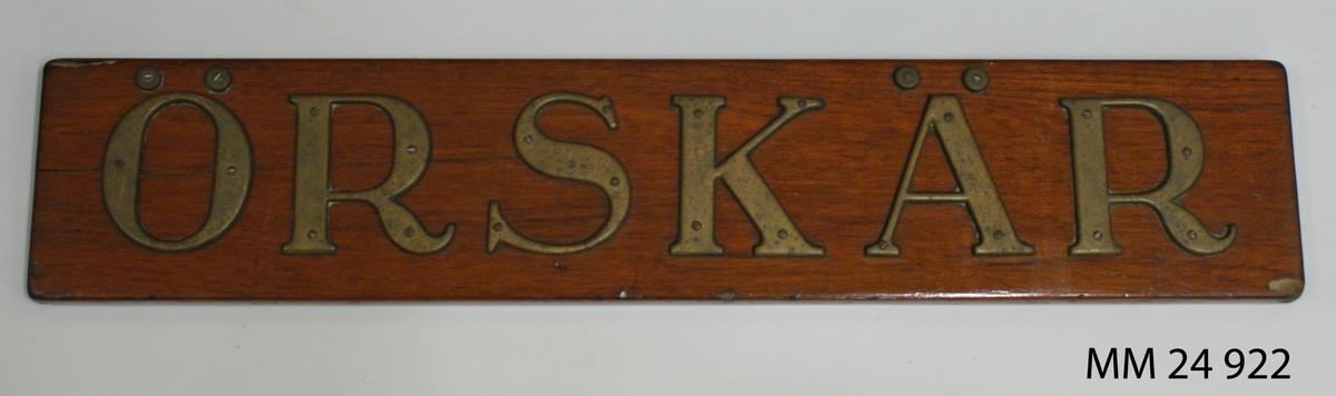 """Namnbräda av teak, fernissad. Bokstäver av mässing med serif. Bokstäverna är fastskruvade från framsidan och bildar namnet: """"Örskär""""."""