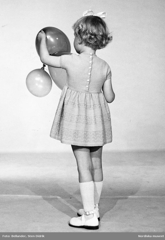 Ett barn i klänning, rosett, knästrumpor och sandaler håller i ballonger.
