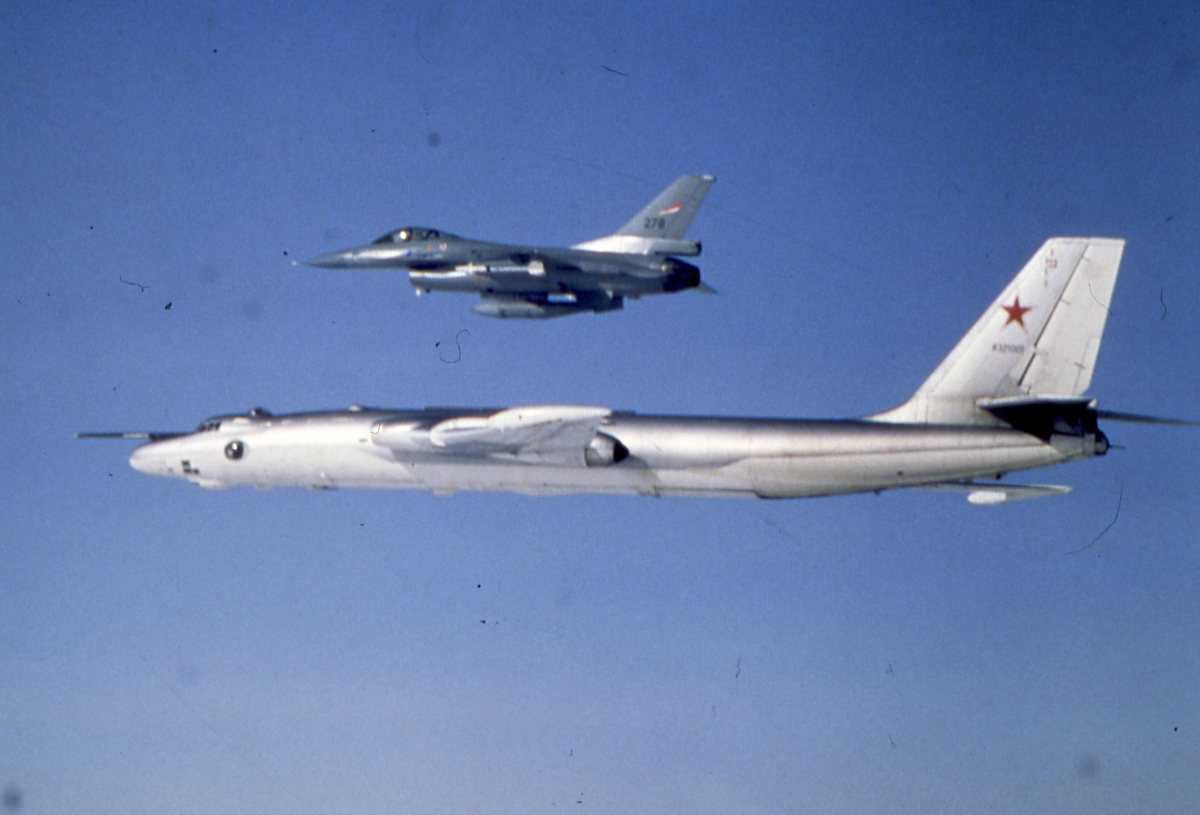 Russisk fly av typen Bison B og over en norsk F-16 med nr. 276.