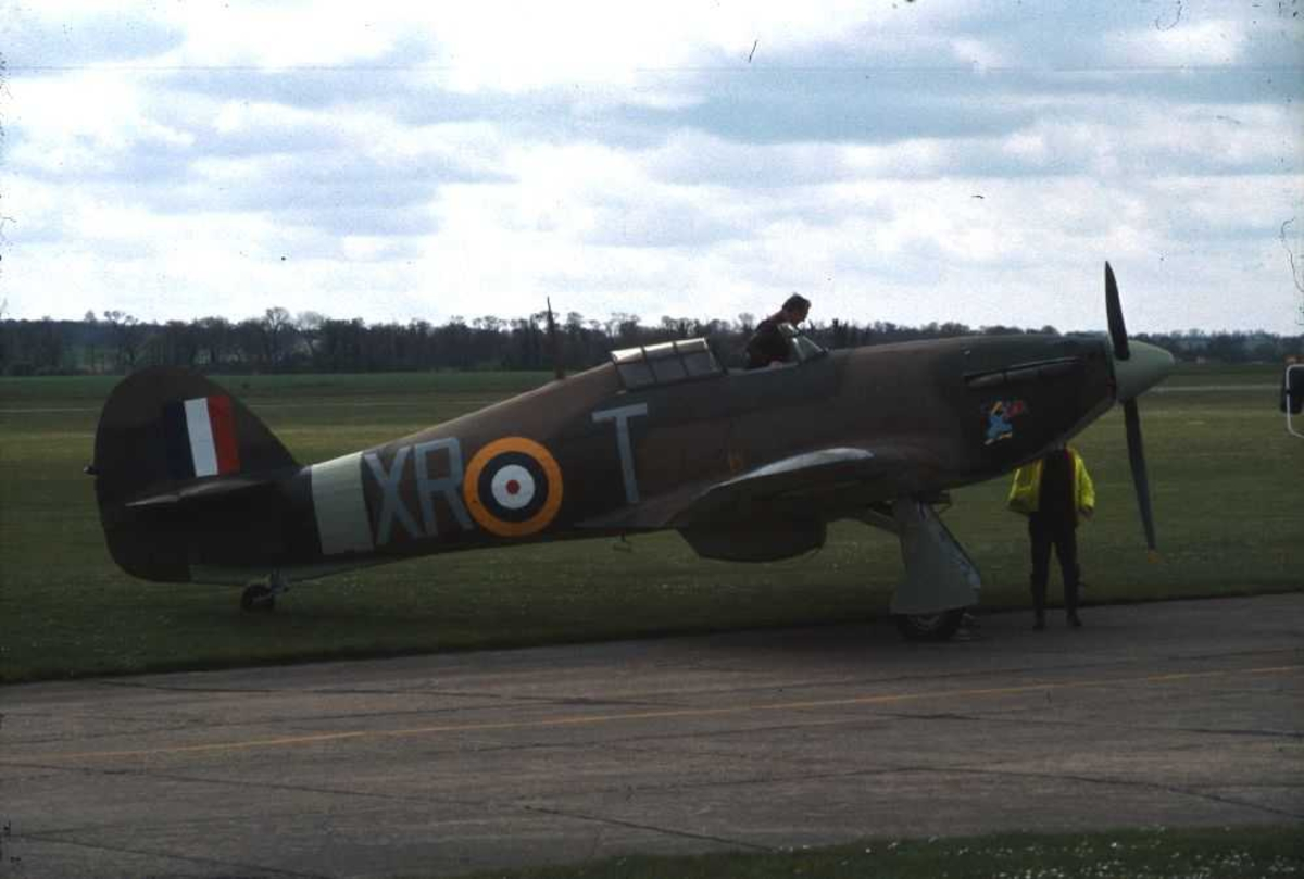 Ett fly på bakken, Hawker Hurricane Mk12A, X-RT. En person i cockpiten og en person ved flyet.