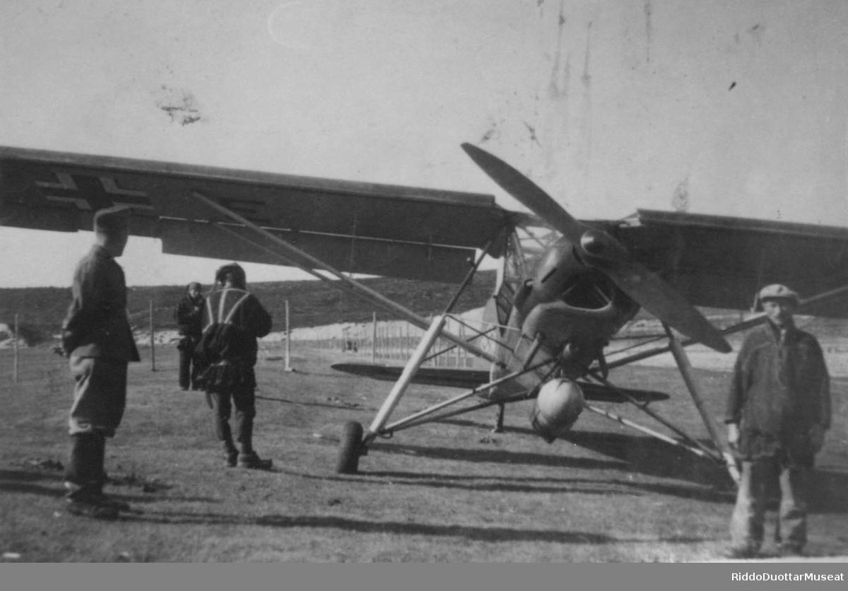 Njeallje dievddu soadjegirdi guoras, Fieseler Storch girdi. Fire menn rundt et propellfly av type Fieseler Storch.