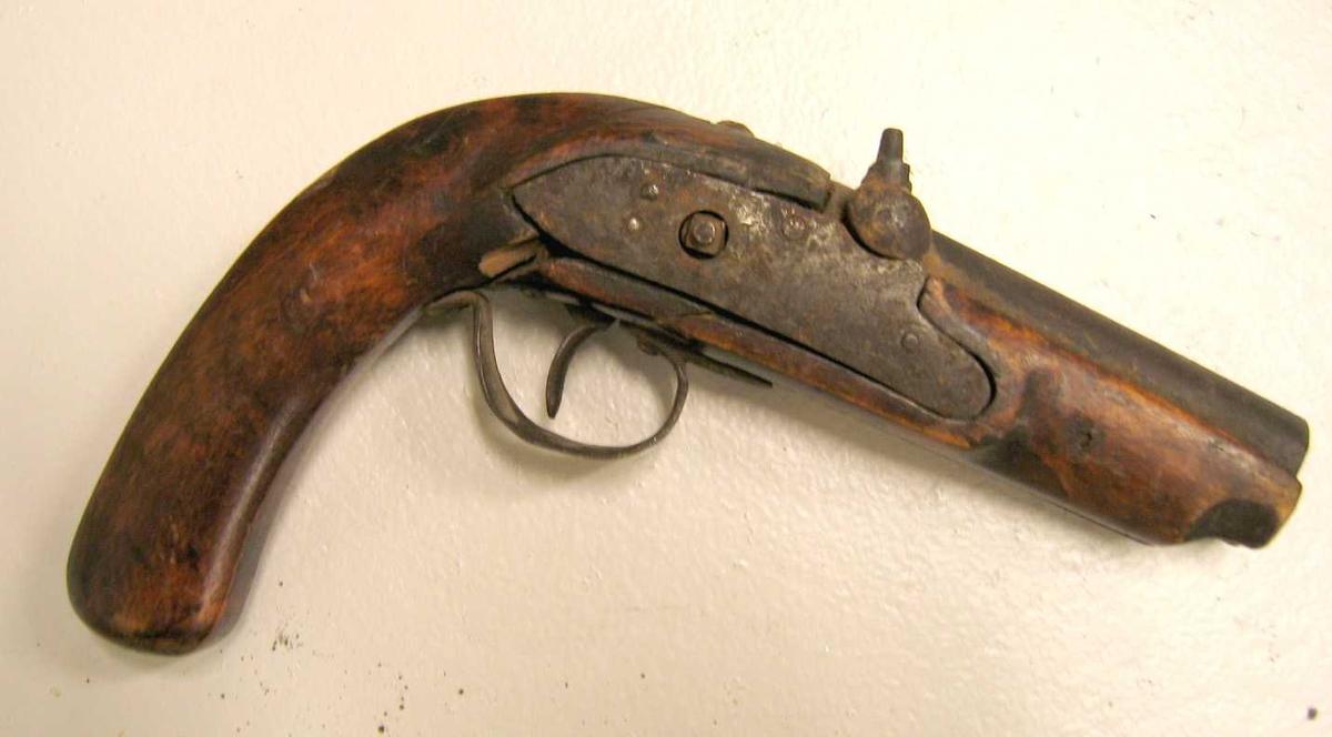 1 pistol  Liten mundladningspistol med helt, poleret skjæft. Løpets længde 9 cm. Hanen mangler. Gave fra gaardbruker Anders Vindedal, Lærdal.