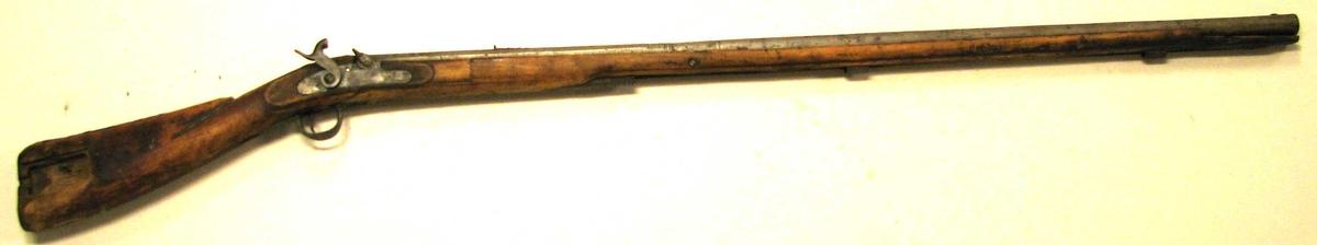 "1 gevær.  Rifle, der i Lærdal har gaaet under navnet ""staalpipa"". Den har oprindelig tilhört en husmand under gaarden Tönjum og har denne nedlagt henved 40 björne med den. Oprindelig har geværet hat flintelaas, der for en del aar tilbake blev ombyttet med knaldlaas. I kolben er utgravert et litet avlangt firkantet rum, hvorover har været skyvelaag. I dette gjemtes reserve bösseflint. Riflen er helskjeftet, har ladestok og er löpet 101 cm langt og indvendig forsynt med 8 rifler. Paa kolben malt med sort 1816 A.J.S.F. og har den messingbeslag.  Gave fra gaardbruker Anders J. Tönjum, Lærdal."