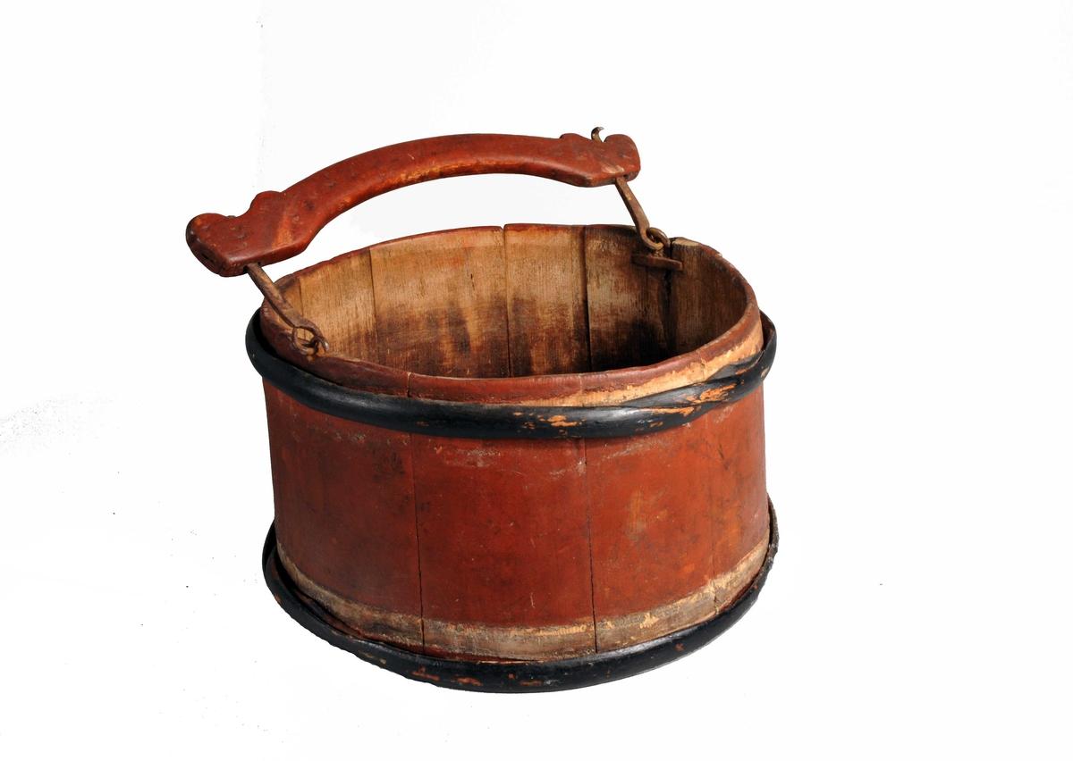 """Form: Rund 1 melkebötte med indfældt """"dvergsten"""" i bunden.  Rund, liten rödmalt melkebötte av furustaver med to sortmalte træbaand. Störelse og type som no 6486 og har som denne indfældt en bergkrystal i bunden forat beskytte de kjör, der melkedes i denne bötte mot yversygdomme.  Kjöpt av O.K. Ellinggaard, Leveld, Aal, Hallingdal."""
