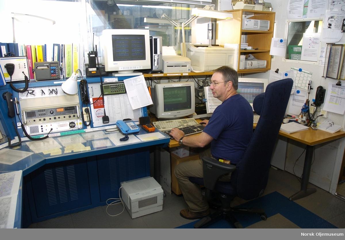 Radiorommet på QP.  Peter Hills, logistics supervisor i arbeid.  Her blir også inn- og utsjekking foretatt samt at han har logistikken på båt- og helikoptertrafikk.