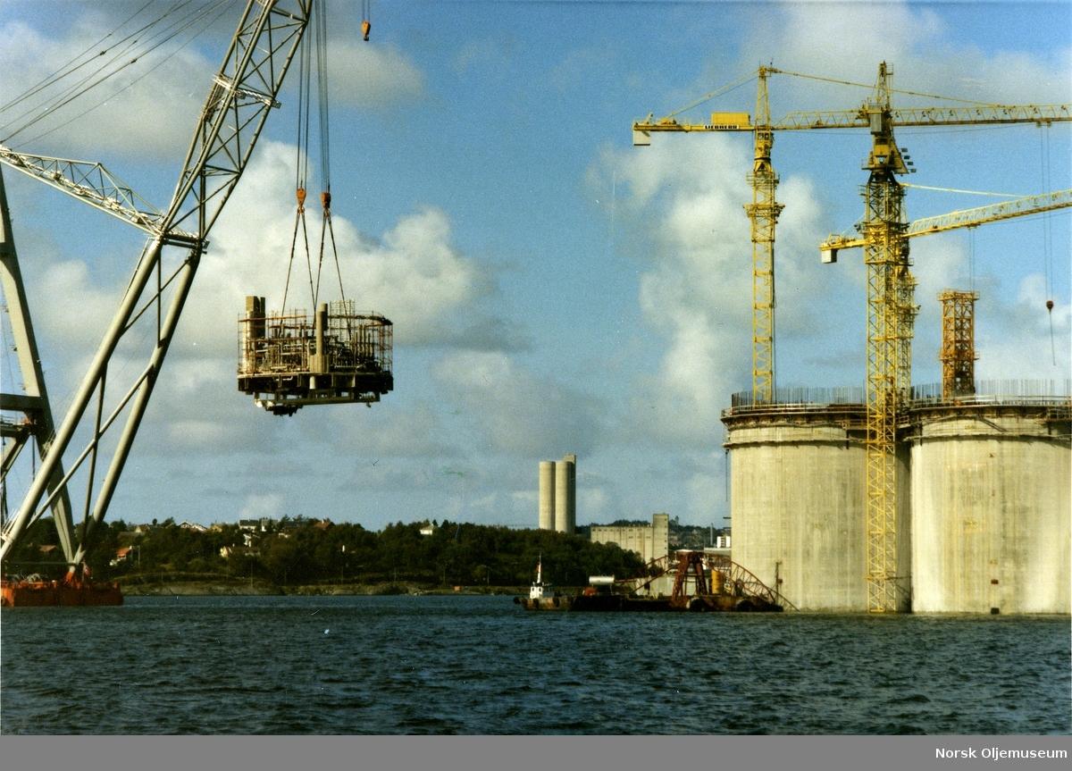 Innløfting av utstyr i et av betongskaftene til Statfjord B, mens  understellet fortsatt er under bygging i Gandsfjorden ved Stavanger..