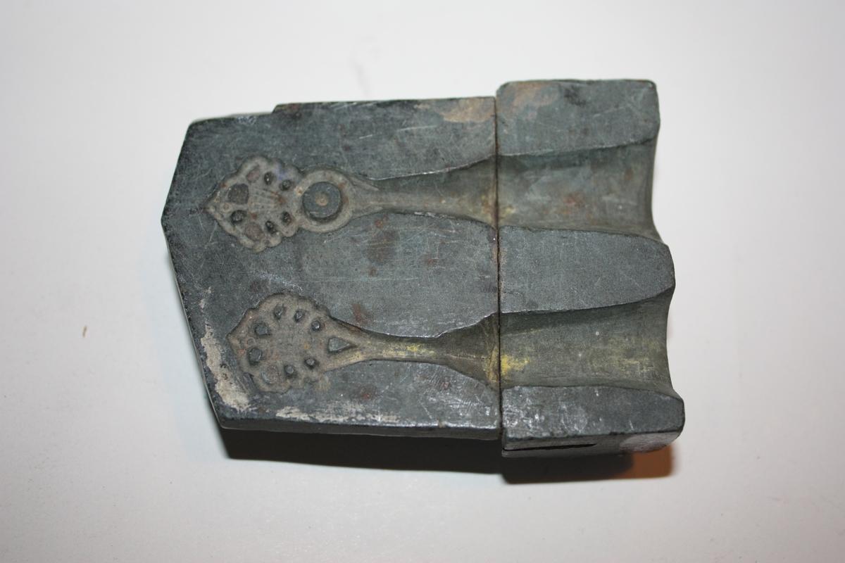 Form: Rektangulær 1 hempeform, 1 hekteform og 1 knappeform. Hempa og hekta er på eine sida, knappeforma på andre sida. Forma består av 2 deler som henger saman ved hjelp av jarn.
