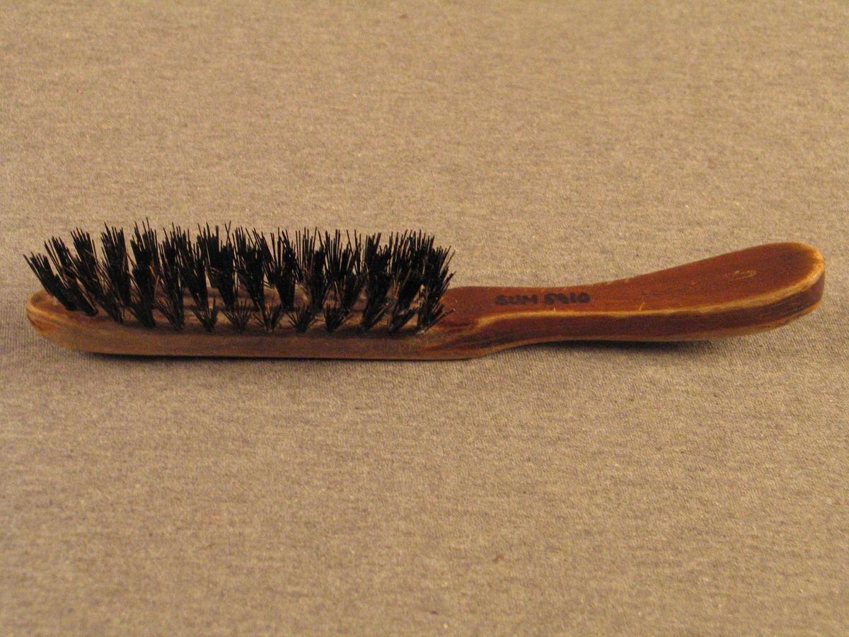 Børste med trehandtak som er forlenga til børstehovud. Haldedelen er forma slik at han gjev handa godt grep, børstehovudet er rett, spissa i enden.