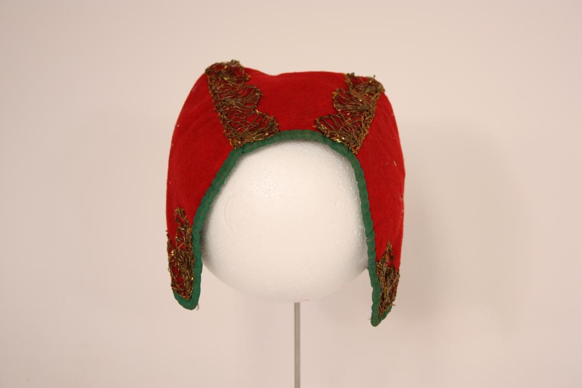Silkekvarding, gullkniplingsband. Har truleg hatt perlebroderi på sidene og midt oppå.