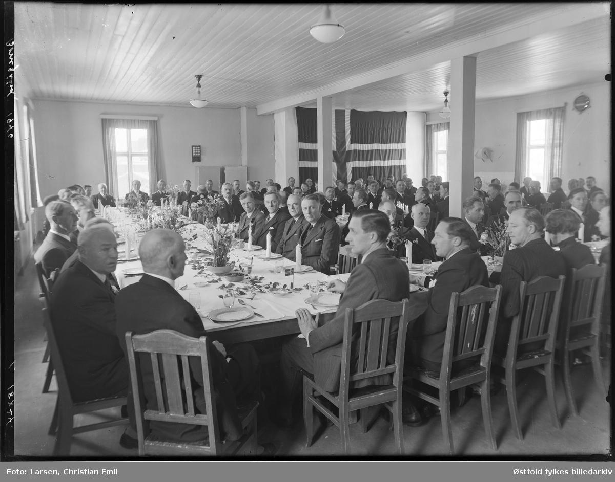 Ukjent gruppe menn rundt dekket festbord, våpenskjold på vegg 1920-1945. Borregaard i Sarpsborg.