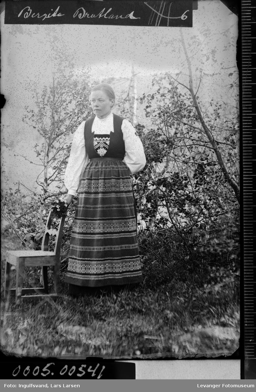 Portrett av en kvinne med bunad i helfigur.