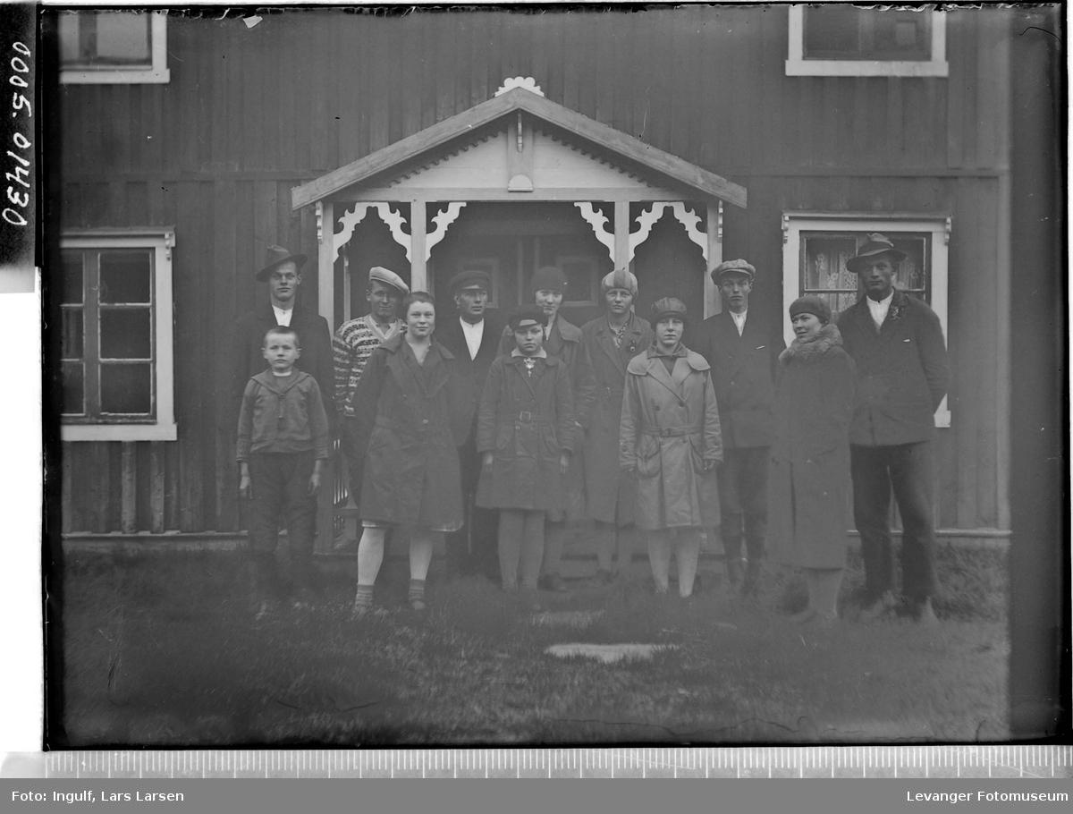 Gruppebilde av elleve ungdommer og en gutt foran et inngangsparti.