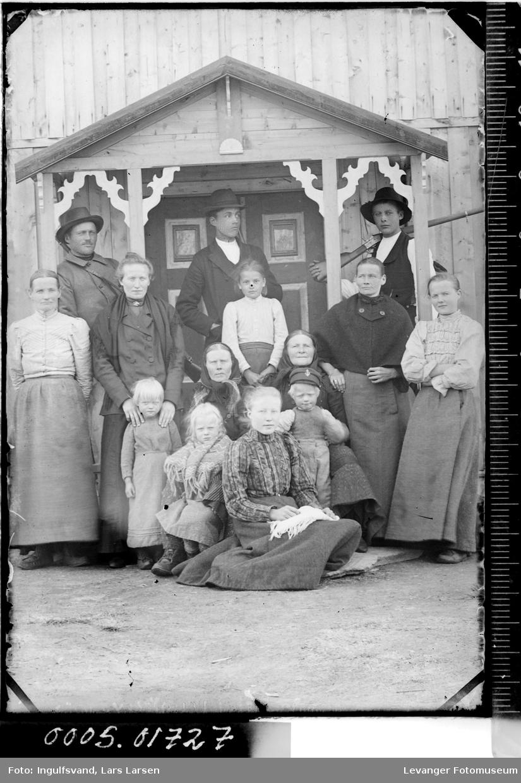 Gruppebilde av syv kvinner, tre menn og fire barn ved et inngangsparti.