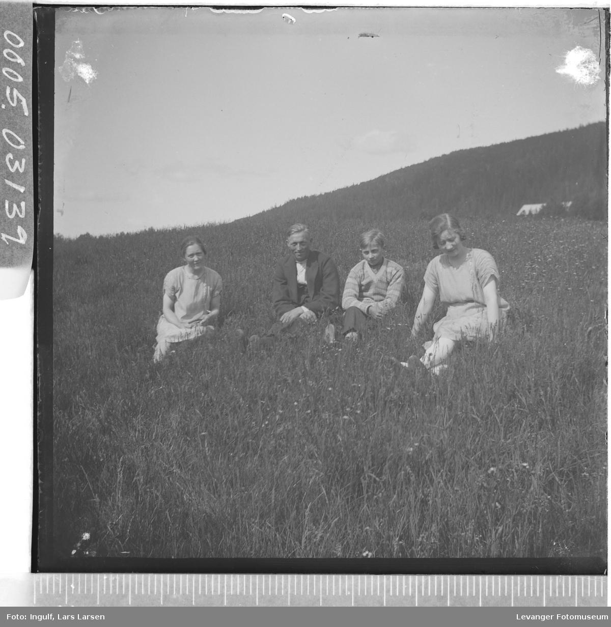 Gruppebilde av to kvinner og to menn sittende i gresset.