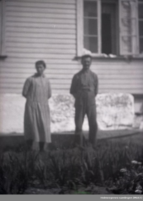 En kvinne og en mann oppstilt foran et bolighus. Antatt samme sted og tidspunkt på ST.K.HE 2010-011-0096 til -0100.