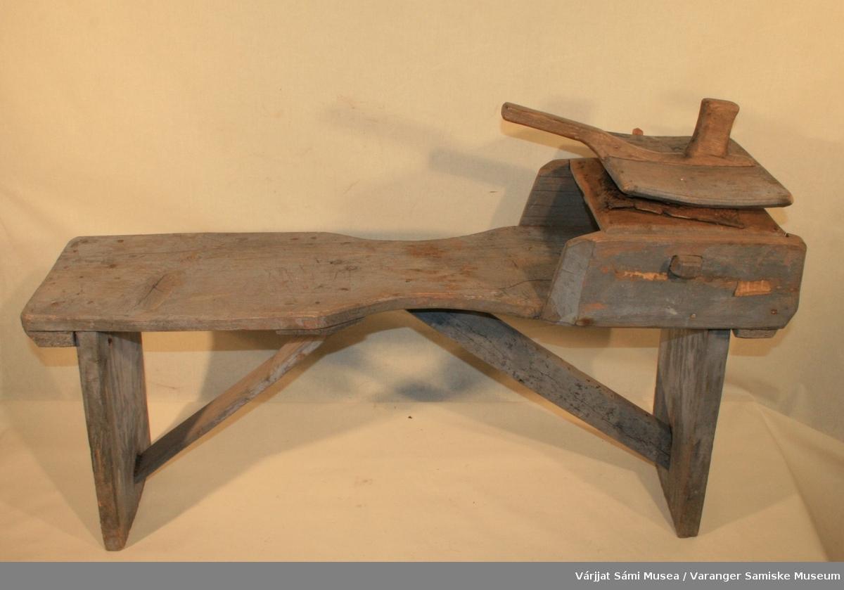 Gråmalt benkekarde av tre. Gjenstanden består av er en lang benk med karde montert fast i enden.