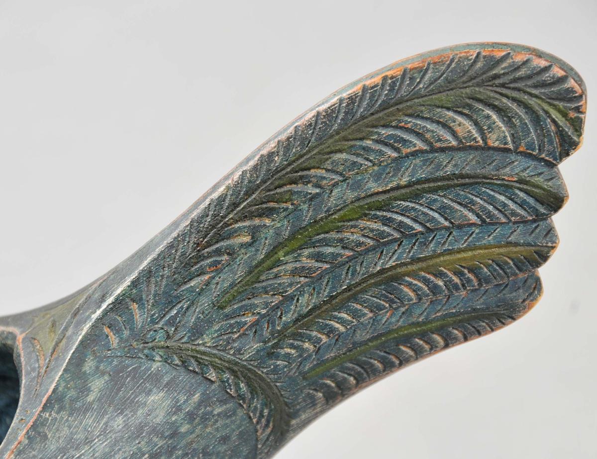 Ølhøne som er måla i ein blågrøn farge både innvendig og utvendig.  Nebb og kam er måla med gulgrønn farge.  Stjerten er dekorera med fire fjør som er skore inn på kvar side.