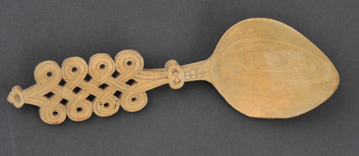 Hjarteforma skeiblad med akantusroser. Handtaket er skore, gjennombrote med dobbel valknuteform.