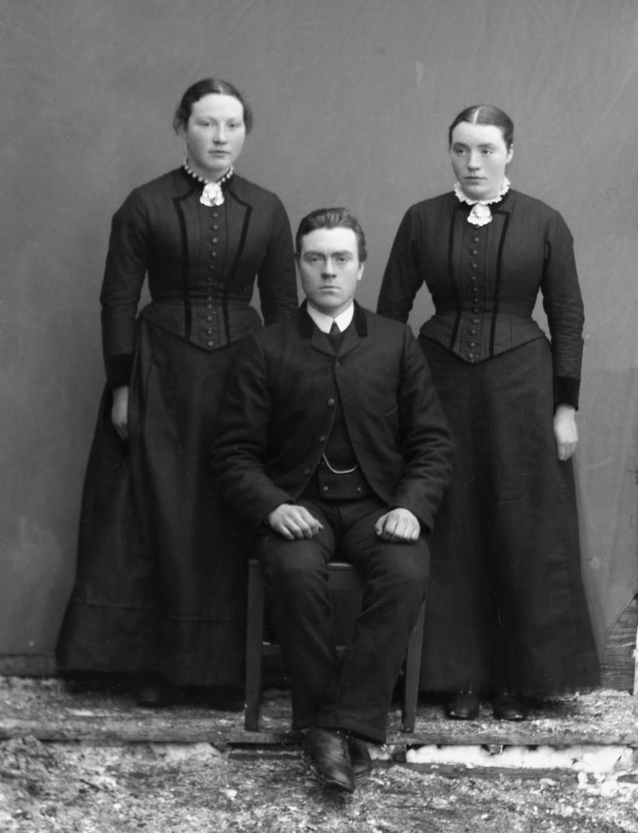 Tre søsken fra Nørre Leine i Vang - to kvinner og en mann. Lerretbakgrunn på tømmervegg. Tynt lag med nysnø.