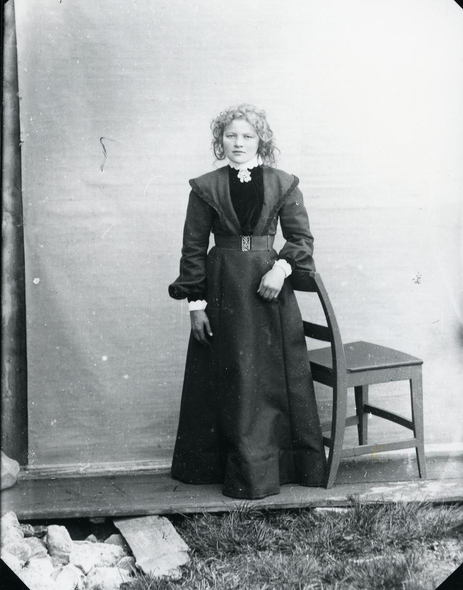 Ung jente ved stol, lerretbakgrunn