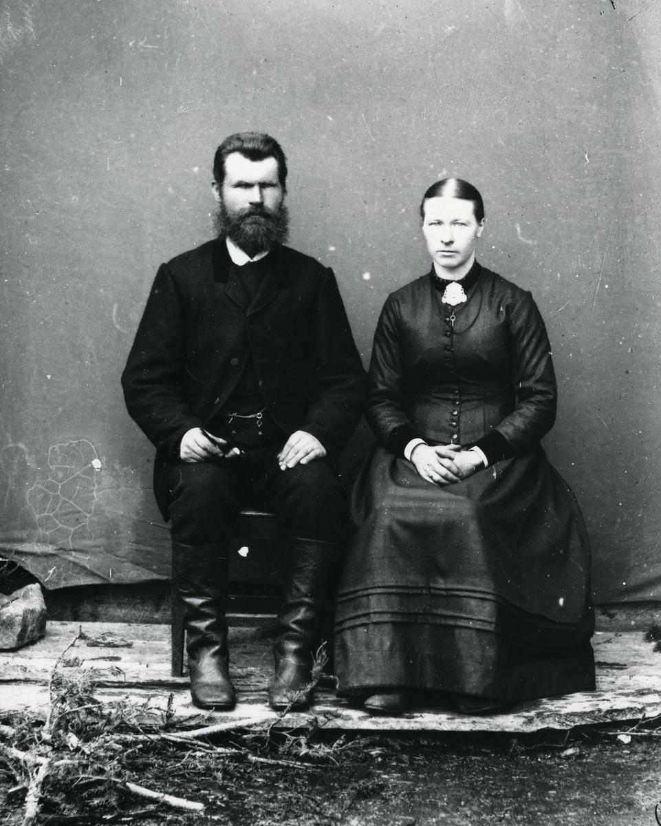Mann i dress og skinnstøvler, og kvinne kledd i mørk kjole, sittende foran lerret