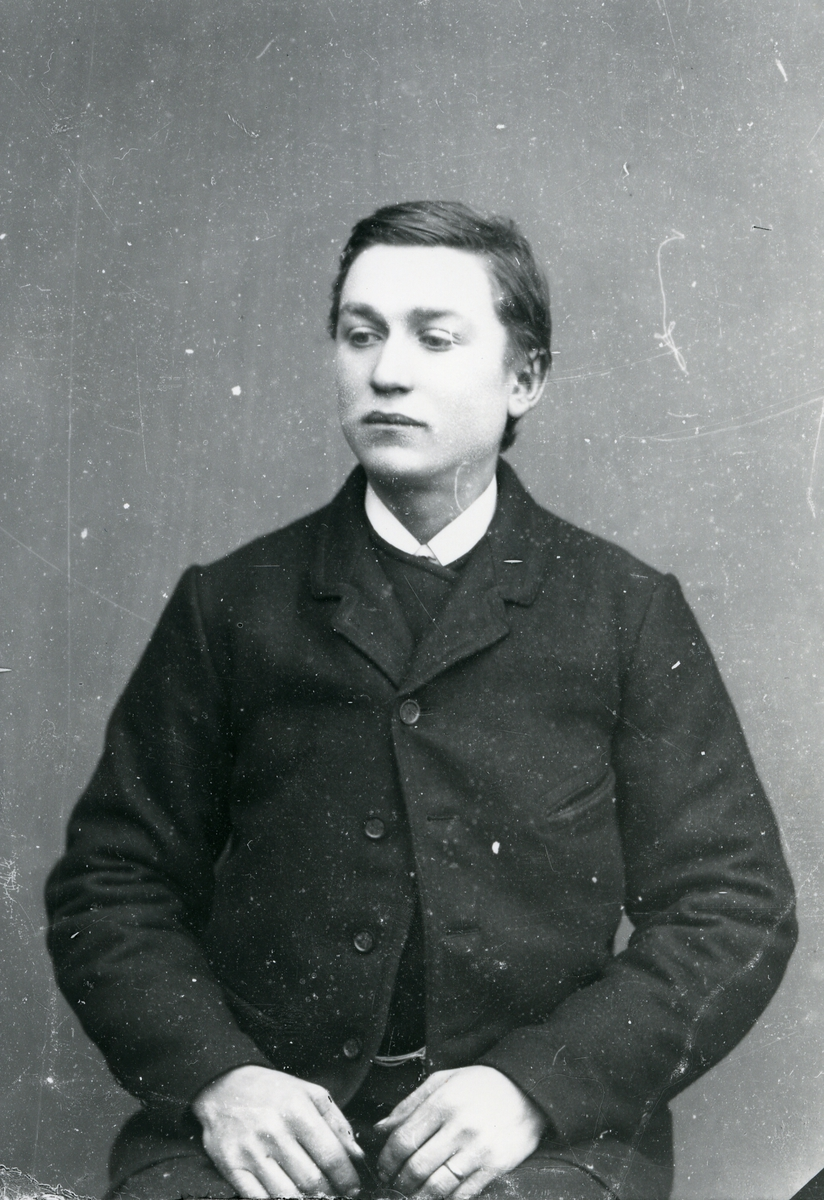 Ung mann i halvfigur, sittende foran lerret