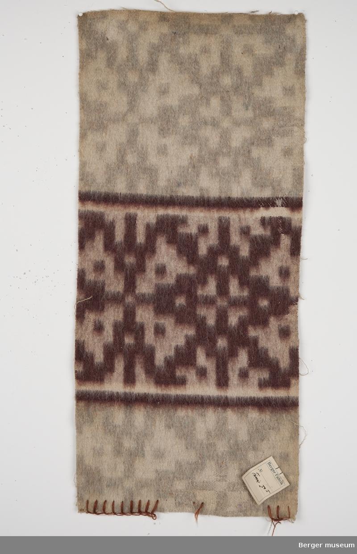 En prøve. Teppe med gjentagende mønster som blir brutt av samme mønsterbord bare at i en annen farge.