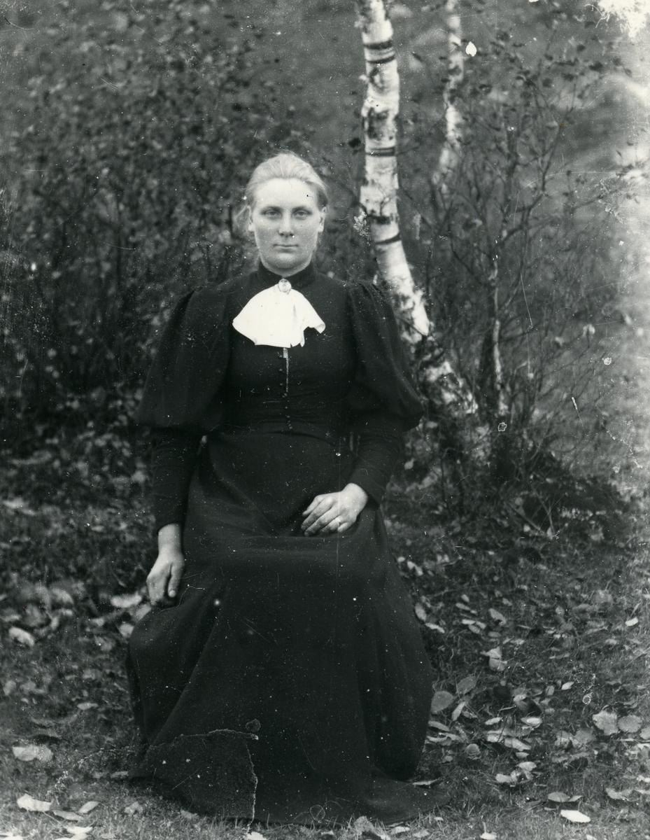 Kvinne sittende på stol, kledd i mørk kjole og kalvekryss, med busker og bjørketrær i bakgrunnen