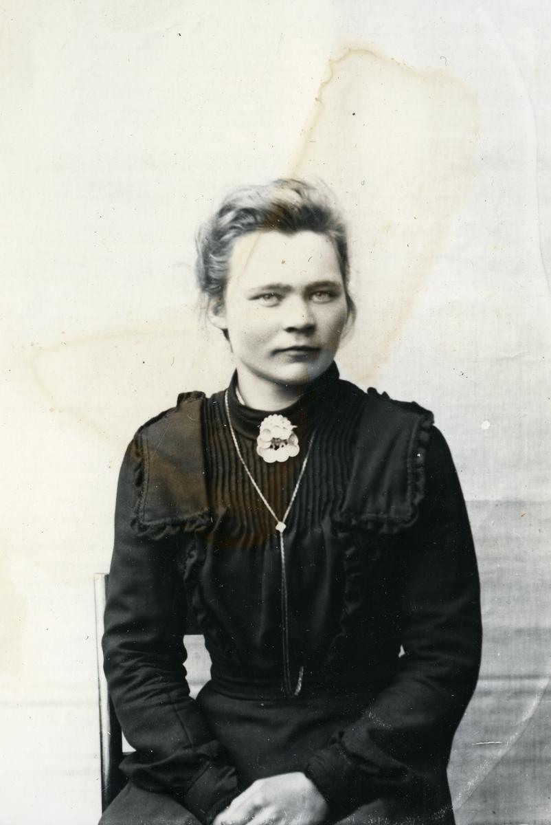 Kvinne sittende foran lerret, fotografert i halvfigur