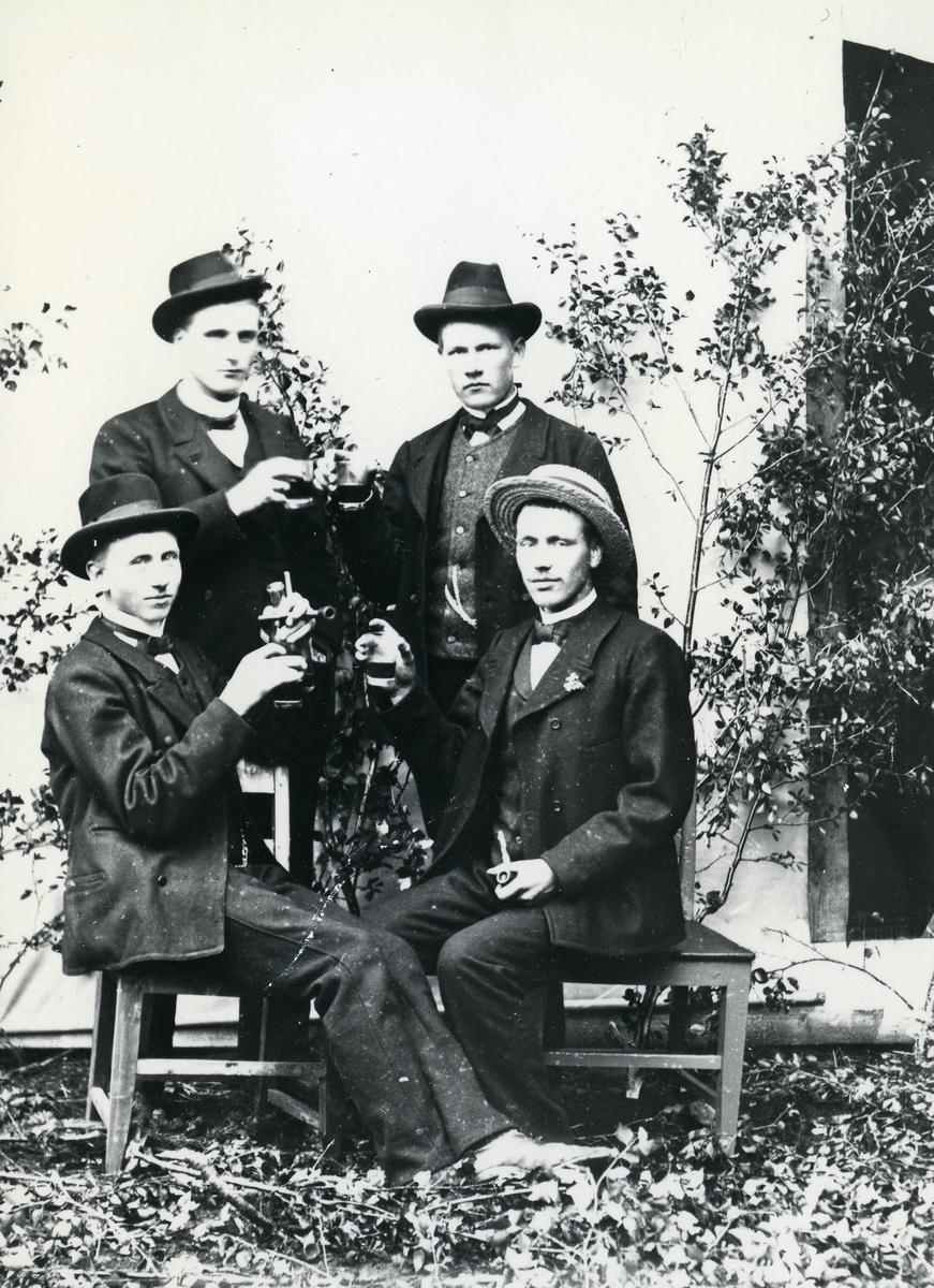 Fire menn kledd i dress og hatt, med glass og piper. Bjørkekvister og lerret som bakgrunn