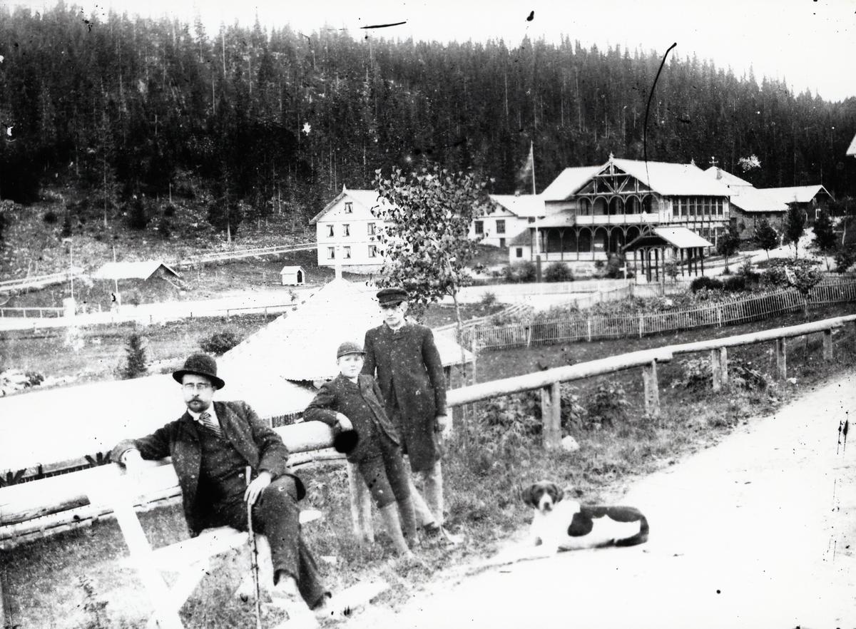 Mann, to gutter og hund, på vei, foran bygninger på Tonsåsen Sanatorium