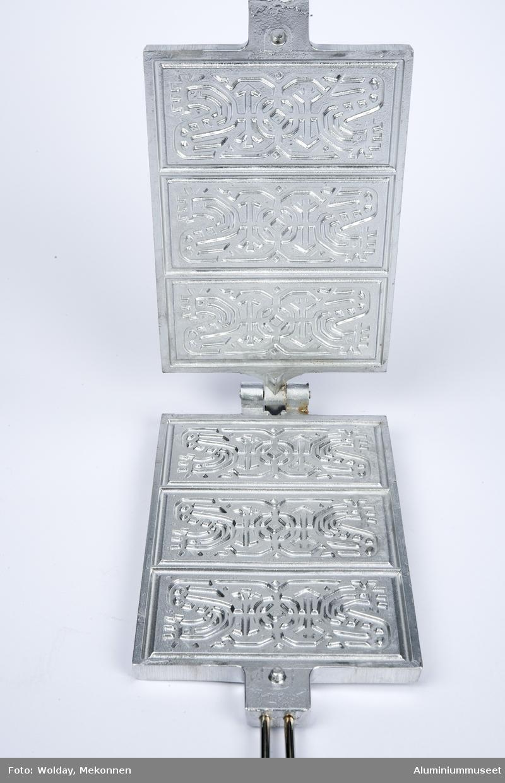 Hengslet jernmed skaft på motsatt kortside. Jernet er delt i tre kakeplater, med en stilisert hane i en folkekunststil. Design av Oskar Sørensen eller Sverre Petersen? Goripannen er pakket inn i silkepapir og plastpose, og det følger med en deigmal.