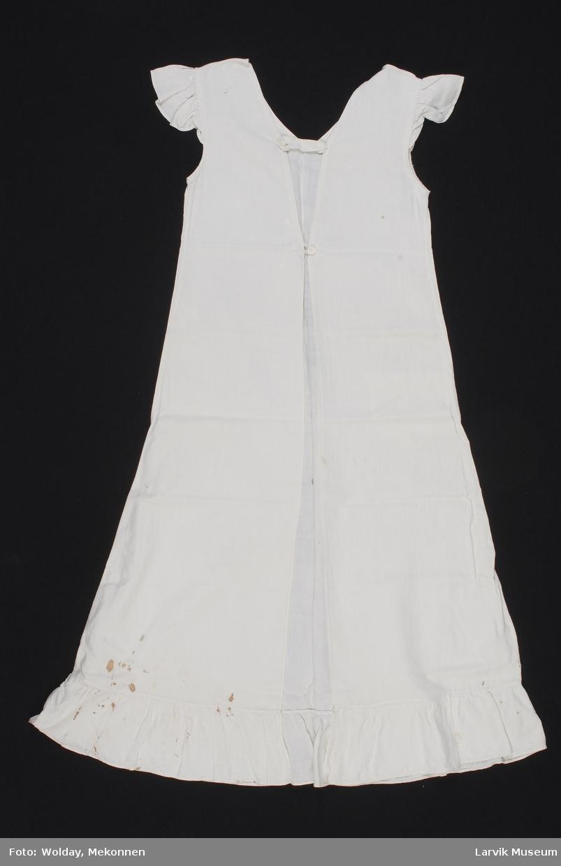 Form: Lang, ser ut som kjole, men er åpen hele veien i den ene enden. Her er det to stropper for å holde sammen forkle. V hals, ermeløs men små kapper på ermene.