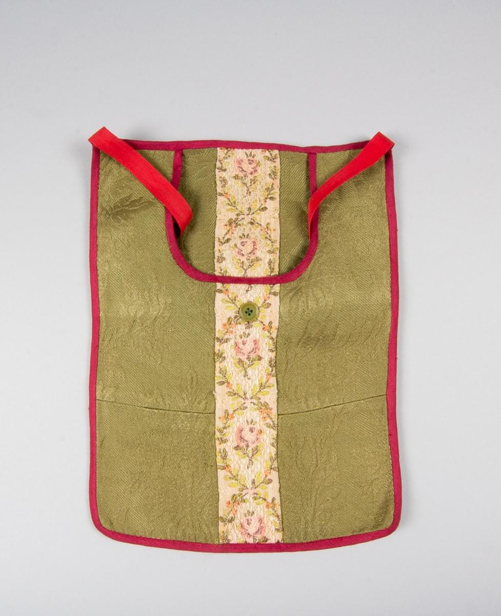 Kjolsäck till dräkt för kvinna från Västra Vingåkers socken, Södermanland. Modell med u-formad öppning. Tillverkad av grönbrunt mönstervävt fabrikstillverkat bomullstyg. I mitten lodrätt ett band troligen klippt från ett mönstervävt tyg med blommor i rosa och grönt på beige botten. Strax under öppningen ett knapphål, sytt med grönbrun tråd. Knappen är grönbrun. Kantat runtom med diagonalvävda röda konstsilkeband. Framstycket ofodrat. Fabriksvävt linnetyg i tuskaft har använts till bakstycke. Midjeband röda, av bomull.