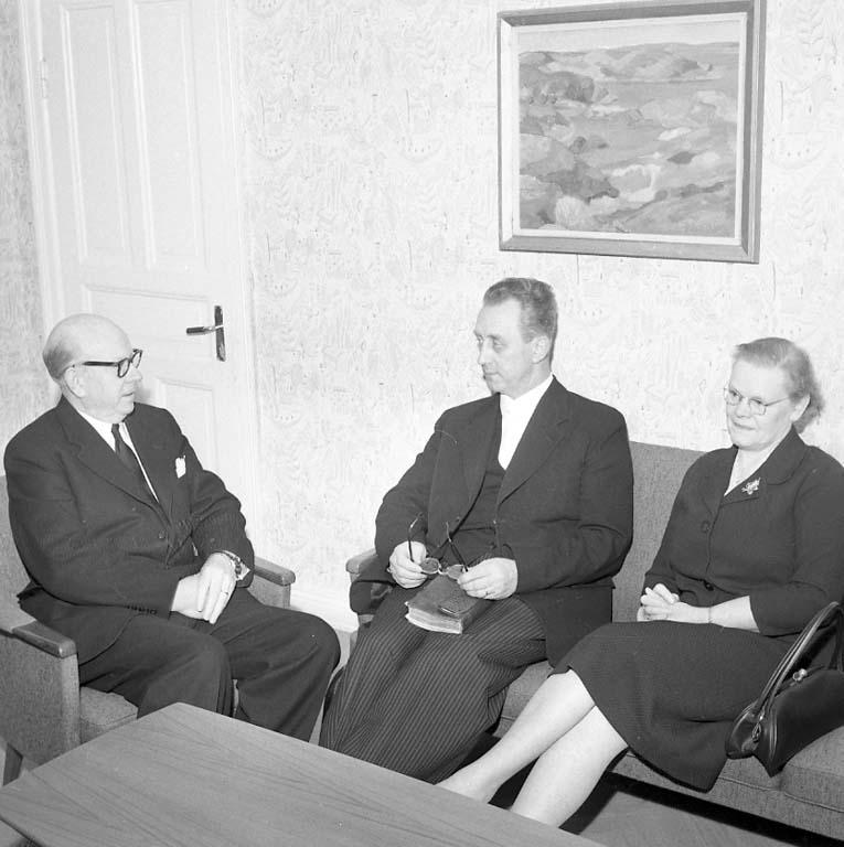 Tre personer sitter i en soffgrupp, från vänster okänd, pastor Bertil Ericsson och hans fru