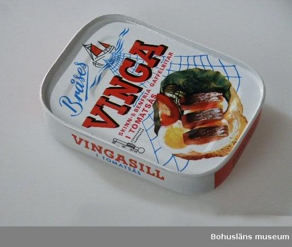"""Rektangulär burk med dekor tryckt på plåten i vitt, rött och blått samt bild av sillsmörgås. Text: """"Bråses Vinga skinn-och benfria gaffelbitar i tomatsås"""". På baksidan samma text och innehållsdeklaration samt """"BRÅSE & SÖNER AB KONSERVFABRIK, KLÄDESHOLMEN"""". Om givaren se UM026667"""