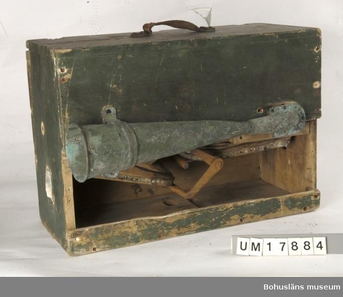 Rektangulär grönmålad låda. På ovansidan är det bärhandtag av läder.   På ena långsidan är det en ljudtratt gjord av koppar.                  Inuti är det två blåsbälgar vilka drivs genom ett vevhandtag vilket är placerat på långsidan där inte ljudtratten är.                         På båda kortsidor är en liten ventil täckt med en metallkåpa.         Ljudtratten hänger löst och på lådsidan där tratten sitter, fattas en bräda, vilket gör att man ser in i lådan.                        Ingår i redskapsbestånd ur sjöbod från Hällsö, Havstenssund, Tanum sn. Se UM017521