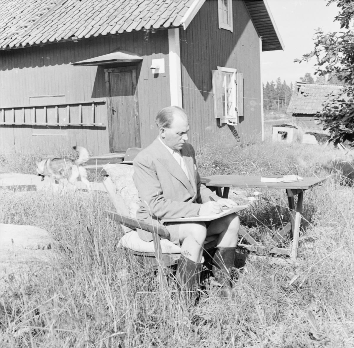 Man sitter på stol i gräset och skriver, Uppland