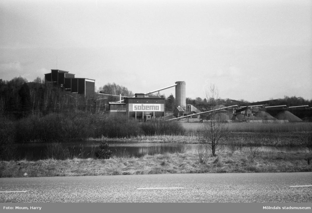 Stenbrottet Sabema i Kållered sett från Gamla Riksvägen över del av Sagsjön, år 1983.  För mer information om bilden se under tilläggsinformation.