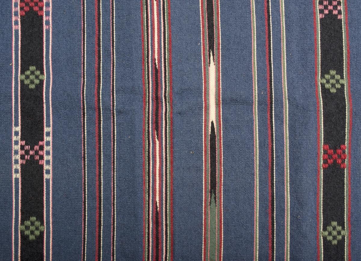 """Vävprov/förklädestyg i inslagsrips och halvkrabba. Gråblå botten med ränder i svart, två nyanser rött och grönt samt rosa och beige/vitt. De bredare svarta ränderna har halvkrabbamönster i rött, rosa och grönt. Några smala ränder har vävts med omväxlande beige/vitt och svart för att ge intryck av ikat/flamgarnsfärgat. Varp i blått 2-trådigt s-tvinnat bomullsgarn, 10 trådar/cm. Inslag i kulört 1-trådigt z-spunnet ullgarn samt i beige/vitt och rosa 2-trådigt s-tvinnat bomullsgarn, ca 20 botteninslag/cm. Två trådar tillsammans i mönsterinslagen. Tyget är ojämnt klippt; längden är 570-1240 mm och bredden 290-810 mm, vävbredden är 810 mm. Vidhängande pappersetikett i ena hörnet med med texten: """"VEMMENHÖG FÖRKLÄDE.""""."""