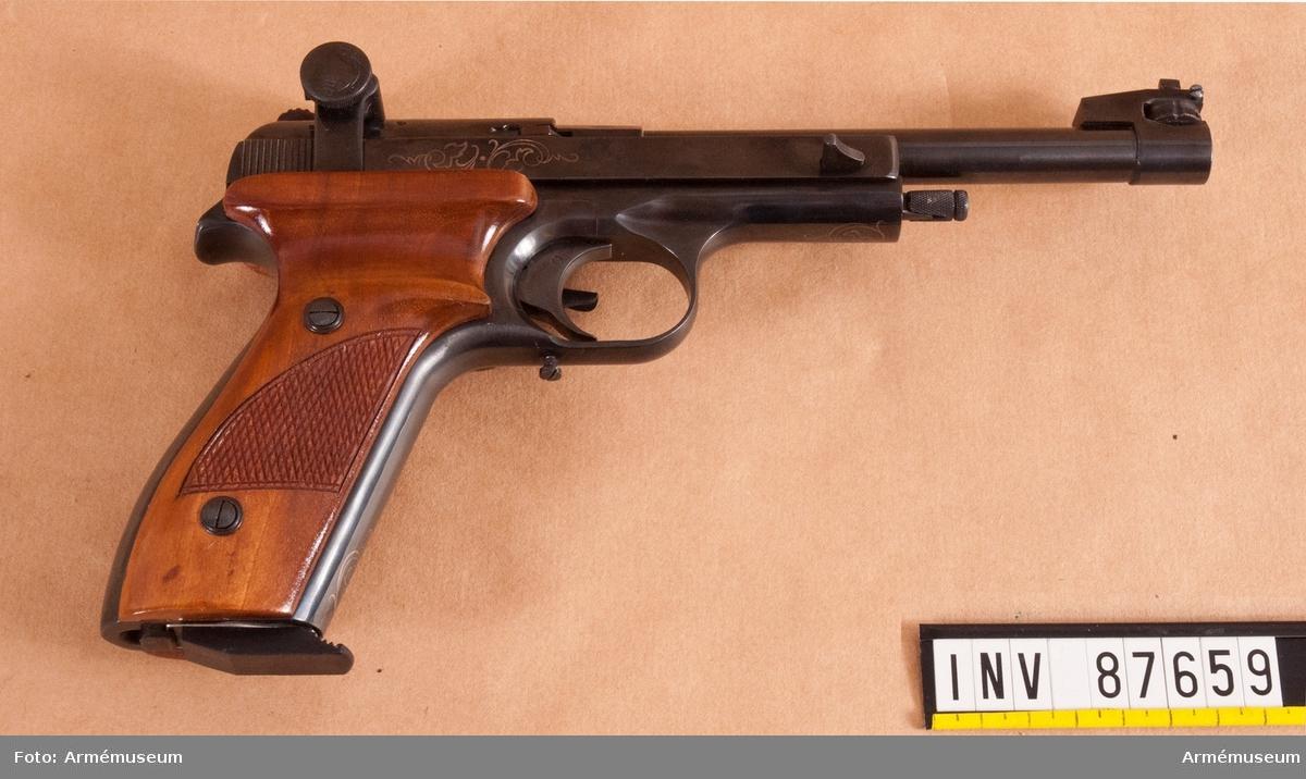 Pistol med tillbehör i schatull av mörkt trä klätt med blå sammet. Magasin med kapacitet för 5 skott.  Kaliber: 5,6x15mmR dvs .22 Long Rifle. Kantantänd ammunition som används för sportskytte och utgör en av världens vanligaste ammunitionstyper.