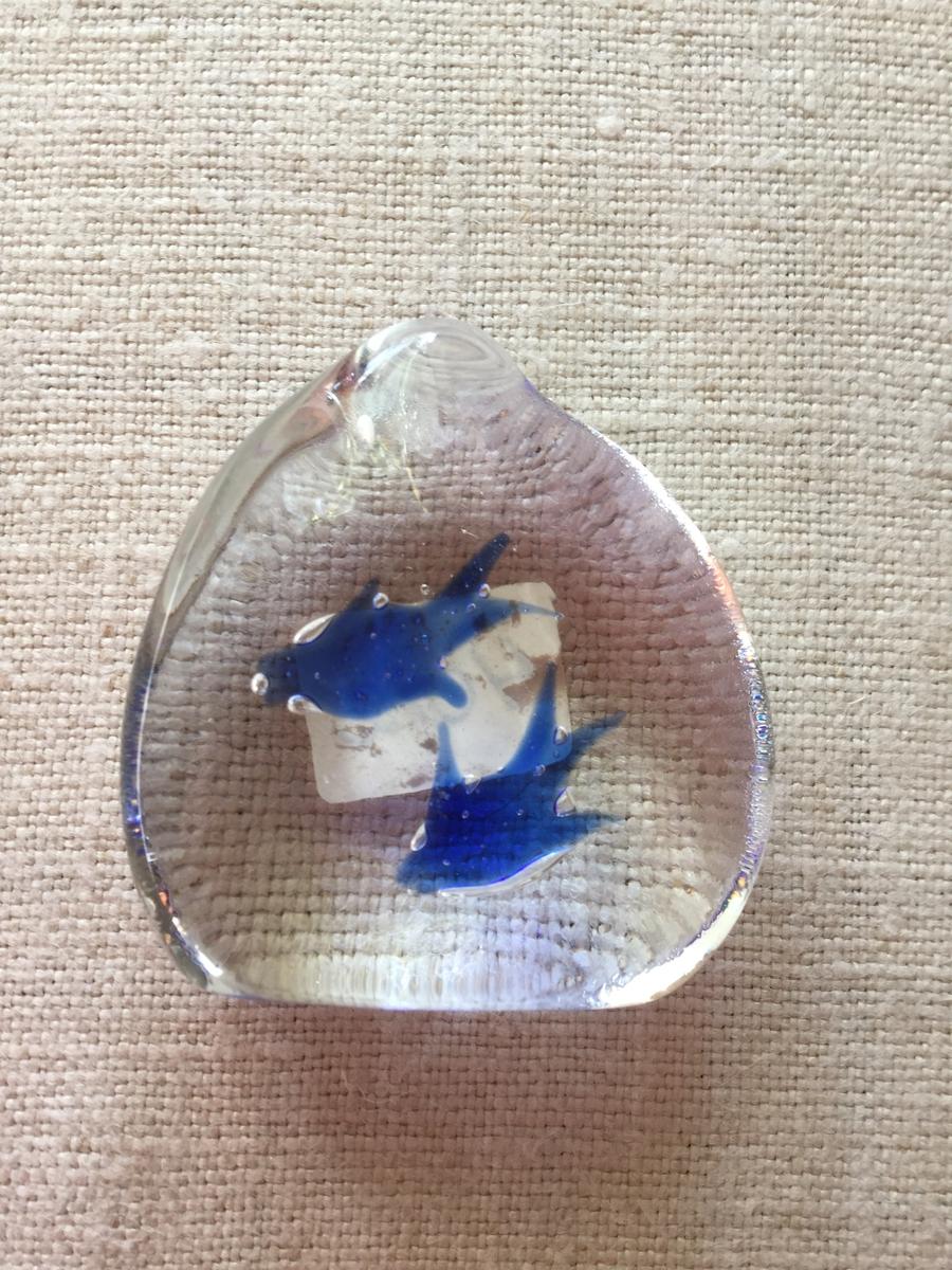 Liten glasprydnad i genomskinligt glas med två blå fåglar ingjutna i glasmassan.