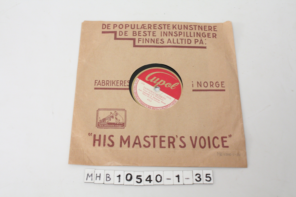 Papiromslaget har en illustrasjon/tegning av en liten hund som sitter å lytter til en grammofon