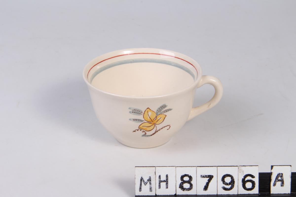 Dekorstripe på  langs munningen på koppen innvendig. Blomst med tre blader fremme og bak på koppen.