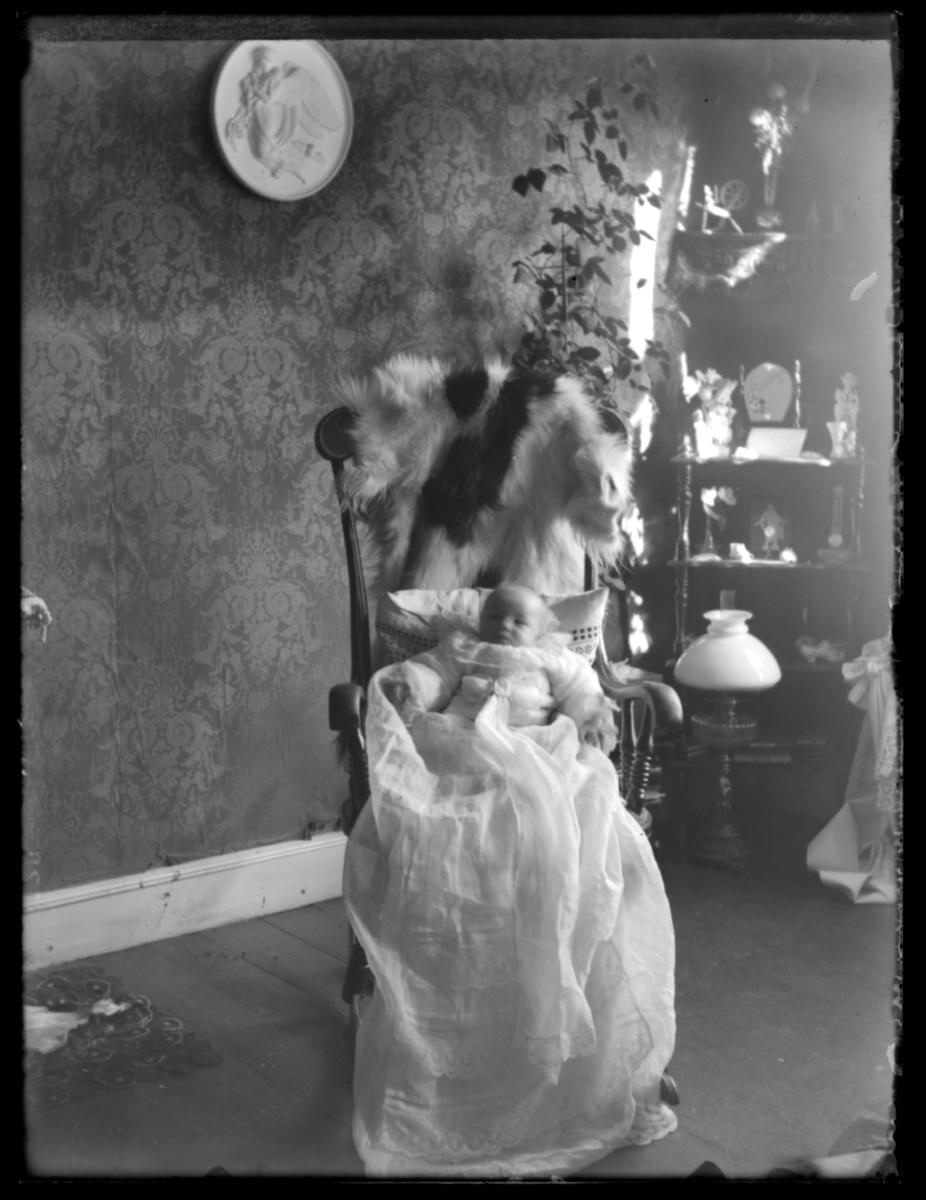 Spedbarn i dåpskjole, fotografert i gyngestol