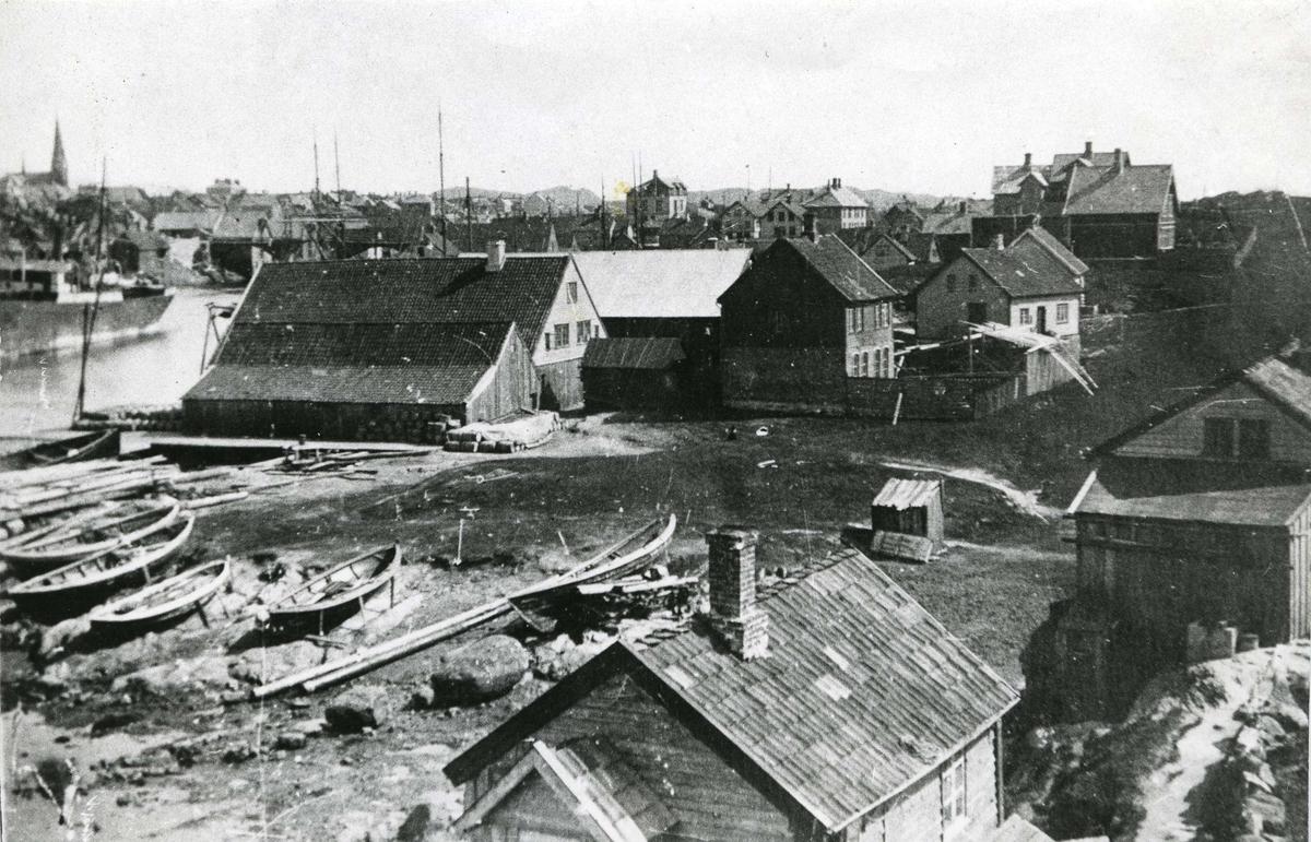 """Østsiden av nordre Hasseløy fotografert i 1903. Det er antagelig fra """"Jordkulå"""", haugen som lå på sørsiden av Svinholmsundet. Nesten alt er nå helt forandret her etter utbyggingen av Flytedokken, Brødr. Lothes dokk og verksted.  Det var Rasmus (""""Visså"""") Olsen som eide det nærmeste huset vi ser på bildet, dengang. Det er senere blitt flyttet til nåv. adresse Holmegt. 76c og er blitt påbygget av eieren nå, Thekla Scheit. Det neste huset , Holmegt. 80, er Hans Jacob, Lisa og Laura Vandaskogs hus, bygget av deres far. Eies nå av Agnes Olsen.  Det nærmeste sjøhuset var Danielsens, deretter Lars Amundsen og våningshus og bak det igjen den gamle spikerfabrikken, bygget i 1901. Alle disse husene er blitt borte etter hvert som Blikkembalasjen bygget ut. Huset på den høge muren, nåv. Holmegt. 77 sto først vegg i vegg med huset sønnenfor, men ble flyttet i 1901. Eier nå er Andr. Scheit. Nabohuset nåv. Holmegt. 73, eide tømmermann Sjur Tordal. Eier nå er Anna Klementsen. Bak det skimtes såvidt Serina Danielsens hus, Holmegt. 65, som eies av Bertr. Hasseløy. Huset med hage i bakken sønnenfor Holmegt. 61 er bygget av bøkker Tindeland ca. 1900.  Plassen som alle færingene ligger på kaltes Sanden. Også den er borte nå."""