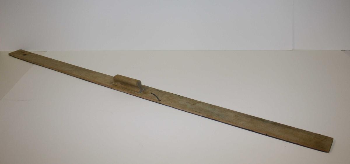 Linjal uten mål. Håndtak på midten, gjennomgående hull i ene enden for oppheng på vegg.